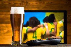 杯啤酒和电视遥控 免版税库存图片