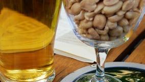 杯啤酒和盐味的penuts在一张木桌的背景在爱尔兰客栈 股票视频