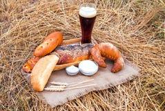 杯啤酒或俄国啤酒和面包在桌布 免版税库存图片