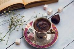 杯土耳其咖啡以土耳其快乐糖和在旧书旁边的心形的巧克力 免版税库存图片