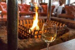 杯在一个温暖和舒适的壁炉前面的白葡萄酒 免版税图库摄影