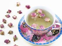 杯在一个白色木板的玫瑰色芽茶 免版税库存图片