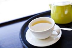 杯在一个盘子的绿茶有茶碟和匙子的 免版税库存照片