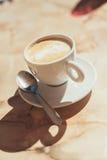 杯在一张木桌上的泡沫的拿铁咖啡 免版税库存照片