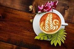 杯在一张木桌上的热奶咖啡 图库摄影