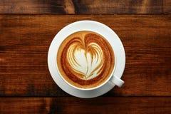 杯在一张木桌上的热奶咖啡 免版税库存图片