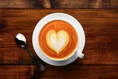 杯在一张木桌上的热奶咖啡 库存照片
