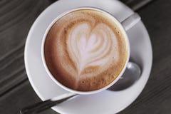 杯在一张木桌上的热的热奶咖啡咖啡 库存照片