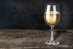 杯在一张木桌上的白葡萄酒 图库摄影
