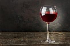 杯在一张木桌上的红葡萄酒 图库摄影
