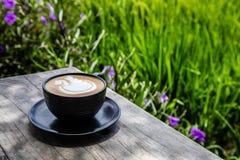 杯在一张桌上的热奶咖啡在稻米边缘的一个开阔地带咖啡馆, Umalas,巴厘岛,印度尼西亚 库存照片