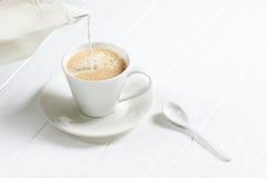 杯在一张白色木桌上的热的热奶咖啡咖啡 库存照片