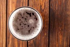 杯在一张老木桌上的低度黄啤酒 顶视图 免版税库存照片