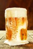 杯在一张老木桌上的啤酒 酒精销售  啤酒广告 免版税库存照片