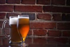 杯在一间黑暗的客栈的低度黄啤酒。 免版税库存照片