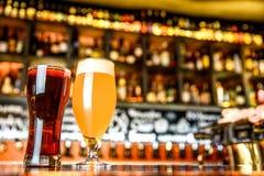 杯在一间客栈的淡和黑啤酒有bokeh背景 免版税库存图片