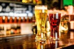 杯在一间客栈的淡和黑啤酒有bokeh背景 库存照片