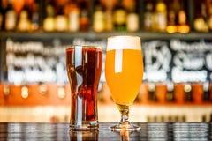 杯在一间客栈的淡和黑啤酒有bokeh背景 免版税库存照片