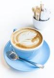 杯在一份热奶咖啡咖啡的拿铁艺术在蓝色杯子 免版税库存照片