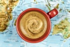 杯在世界地图的新鲜的泡沫的咖啡 免版税库存图片