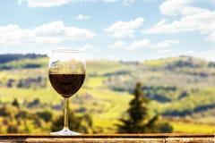 杯在壁架俯视的葡萄园的酒在Chianti意大利 图库摄影