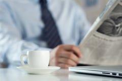 杯在工作台的早晨咖啡有商人读书新闻的 图库摄影
