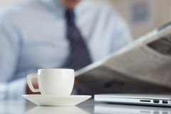 杯在工作台的早晨咖啡有商人读书新闻的 库存照片