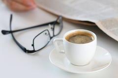 杯在工作台的早晨咖啡有玻璃和报纸的 图库摄影