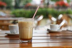 杯在木桌上的冷的被冰的拿铁 库存照片
