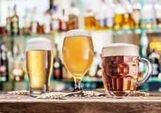 杯在木桌上的啤酒 在背景的被弄脏的客栈内部 库存照片