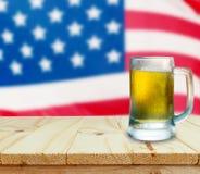 杯在木桌上的啤酒 背景烟花标志夜空满天星斗的美国 免版税图库摄影