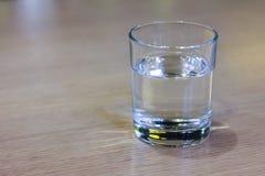 杯在木桌上的清楚的水 免版税库存图片
