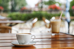 杯在木桌上的热奶咖啡在街道咖啡店 免版税图库摄影
