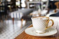 杯在木桌上的热的咖啡在咖啡店backgro 免版税库存图片
