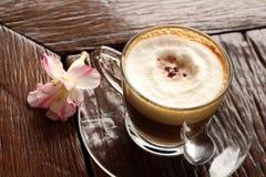 杯在木桌上的热的拿铁咖啡 库存照片