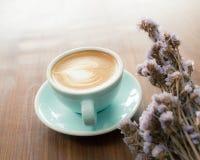 杯在木桌上的热的拿铁艺术咖啡 库存照片