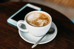 杯在木桌上的热的拿铁艺术咖啡 库存图片