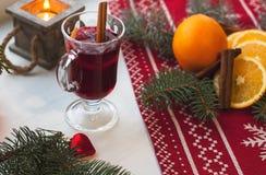 杯在木桌上的热的被仔细考虑的酒与蜡烛、桔子、桂香和圣诞树 免版税图库摄影