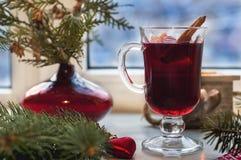 杯在木桌上的热的被仔细考虑的酒与蜡烛、桔子、桂香和圣诞树 图库摄影