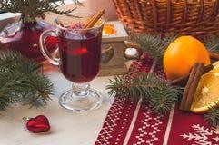 杯在木桌上的热的被仔细考虑的酒与蜡烛、桔子、桂香和圣诞树 免版税库存照片