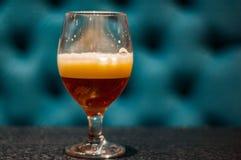 杯在木桌上的琥珀色的麦酒啤酒在与拷贝空间的酒吧 库存照片