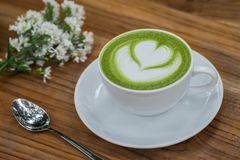 杯在木桌上的绿茶拿铁 库存照片