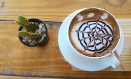 杯在木桌背景的热奶咖啡 免版税图库摄影