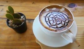 杯在木桌背景的热奶咖啡 免版税库存照片