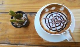 杯在木桌背景的热奶咖啡 图库摄影