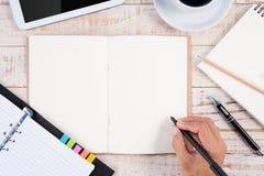 杯在木桌ba的热的咖啡和人手文字笔记本 免版税图库摄影