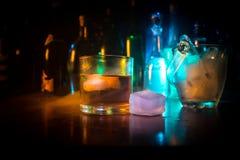 杯在木酒吧特写镜头的威士忌酒与瓶弄脏了在黑暗的背景的看法与光和烟 杯威士忌酒 免版税库存照片