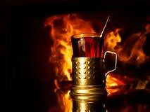杯在杯座的茶由壁炉 免版税库存照片