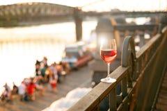 杯在栏杆的红葡萄酒与日落在布拉格市 业余时间的概念在城市和饮用的酒精的 免版税库存照片