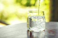 杯在桌上的清楚的水 免版税库存图片